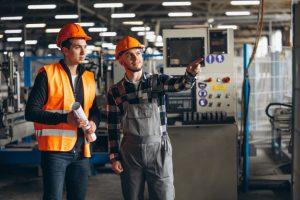 técnico em automação explica funcionamento de máquina a outro profissional