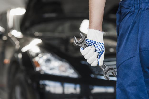 técnico em manutenção automotiva com macacão e ferramenta na mão