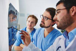 três homens veem resultado de radiografia