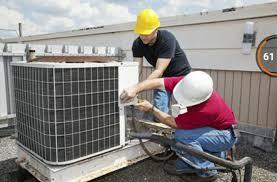 dois técnicos em refrigeração consertando ar-condicionado