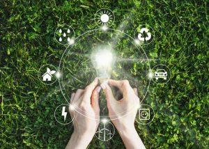 imagem mostra ícones de energia sobre uma grama verde e as mãos de uma pessoa