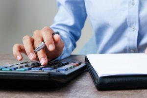 homem com calculadora e agenda nas mãos